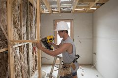 Young builder industry trainee man on his 20s wearing protective helmet learning working with drill at industrial workshop site. In carpenter and renovation Royalty Free Stock Images