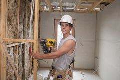 Young builder industry trainee man on his 20s wearing protective helmet learning working with drill at industrial workshop site. In carpenter and renovation Royalty Free Stock Photo