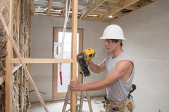 Young builder industry trainee man on his 20s wearing protective helmet learning working with drill at industrial workshop site. In carpenter and renovation Stock Images