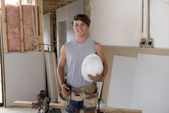 Young builder industry trainee man on his 20s wearing protective helmet learning working at industrial workshop site. In carpenter and renovation technician Royalty Free Stock Image