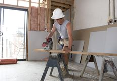 Young builder industry trainee man on his 20s wearing protective helmet learning working at industrial workshop site. In carpenter and renovation technician Stock Photo