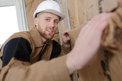 Young builder insulating walls in room Stock Photography