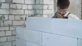 Young builder in protective glasses laying block at construction site stock video footage
