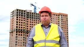 Young builder says No. By shaking his head. Worker says No, meaning No. Construction site.  stock footage