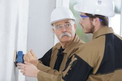 Young builder and teacher sanding wall indoors. Sanding royalty free stock photography