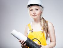 Young builder woman construction worker, blueprints plan Royalty Free Stock Images