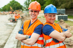 Young builders in helmets. Image of happy young builders in helmets at work royalty free stock images