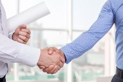 Young builders made deal concerning a new project. Close up of arms of architect and foreman shaking hands. The new plan was approved. They built a consensus Royalty Free Stock Image