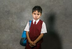 Young bullied abused schoolboy in uniform carrying school bag sad depressed on blackboard feeling a lonely and stressed kid victim. Young bullied and abused royalty free stock photos