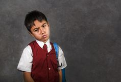 Young bullied abused schoolboy in uniform carrying school bag sad depressed on blackboard feeling a lonely and stressed kid victim. Young bullied and abused royalty free stock photography