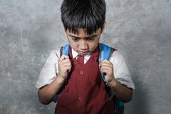 Young bullied abused schoolboy in uniform carrying school bag sad depressed on blackboard feeling a lonely and stressed kid victim. Young bullied and abused royalty free stock images