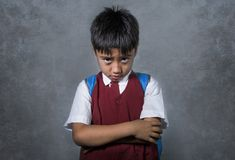 Young bullied abused schoolboy in uniform carrying school bag sad depressed on blackboard feeling a lonely and stressed kid victim. Young bullied and abused stock image