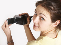 Young bunette girl holding video camera. Young brunette on isolated background holding video camera looking back Royalty Free Stock Image