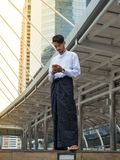 Young Burmese businessman using mobile phone to find a data for. His business stock photo