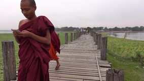 Young Burmese monks in red clothes walking. On Ubein Bridge, Mandalay, Myanmar stock video