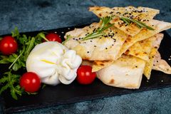 Young burrata cheese. With focaccia bread royalty free stock photo
