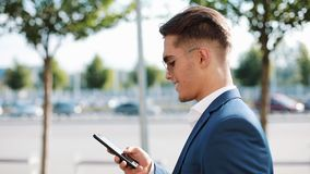 Young businesman in sunglasses talking on his phone and walking in the street. Successful life. Business style, traveler. Communication, modern lifestyle stock video footage