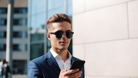 Young businesman in sunglasses using smartphone and walking in the street. Successful life. Business style, traveler. Communication, modern lifestyle. Active stock video