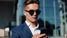 Young businesman in sunglasses using smartphone and walking in the street. Successful life. Business style, traveler. Communication, modern lifestyle. Active stock video footage