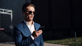 Young businesman in sunglasses using smartphone and walking in the street. Successful life. Business style, traveler stock video