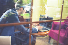 Young businesman working at cafe, using laptop. Throuhg the window Royalty Free Stock Image