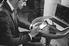 Young businesman working at cafe, using mobile phone. And laptop. Black and white image. Through the window Stock Images