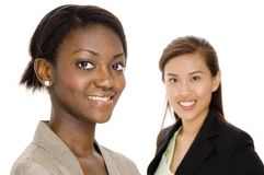 Young Business. An attractive young black woman standing in front of her asian colleague Royalty Free Stock Image