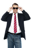 Young business achiever holding shades in style Royalty Free Stock Photos