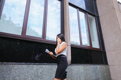 Young business asian female walks and talks on phone, holds docu Royalty Free Stock Photo