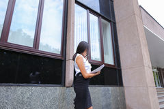 Young business asian female walks and talks on phone, holds docu Stock Image