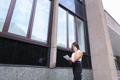 Young business asian female walks and talks on phone, holds docu Royalty Free Stock Photos