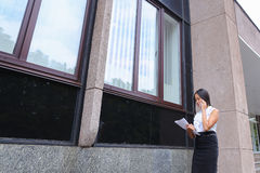 Young business asian female walks and talks on phone, holds docu. Successful young business asian woman walks and talks on phone, holds and looks at documents Stock Images
