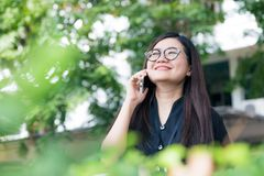 Young business asian women use cellphone in green park Stock Photo