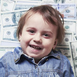 Young business baby girl lying in money. People, dollar, money,. Wealth and rich Stock Images