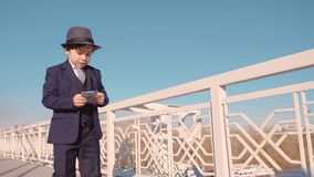 Young business boy in black suit and hat throwing money from bridge. Waste money stock video