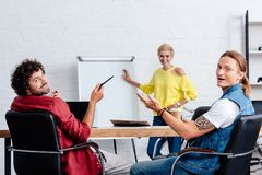 Young business colleagues discussing new project and smiling at camera. In office stock photos
