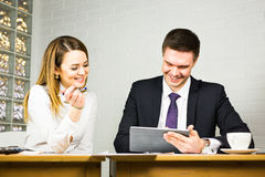 Young business colleagues discussing work on a laptop computer in co-working space, corporate businesspeople. Two office workers talking in an office interior Royalty Free Stock Photo