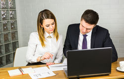 Young business colleagues discussing work on a laptop computer in co-working space, corporate businesspeople Stock Photo