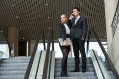 Young business couple on escalator. Stock Image