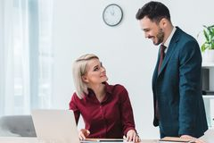 Young business colleagues smiling each other while working together. In office stock photography