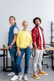 Young business colleagues standing together and smiling at camera in office royalty free stock photo