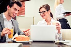 Young Business Couple In A Cafe. A young business couple is discussing important figures over their breakfast Stock Photo