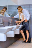 Young business couple flirting with each other at office washroom Stock Photos