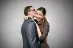 Business love pair. Young business couple is kissing and smiling isolated on gray background. Loving relationships at work concept royalty free stock photography