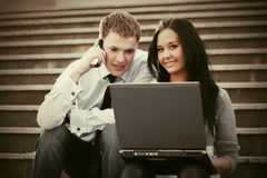 Young business couple with laptop on the steps Royalty Free Stock Photos