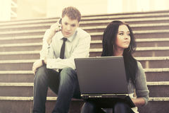 Young business couple with laptop on the steps Stock Images
