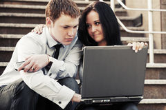 Young business couple with laptop on the steps Royalty Free Stock Images
