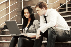 Young business couple with laptop on the steps Stock Photos