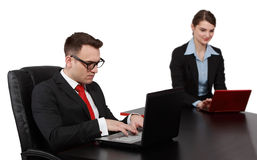 Young Business Couple on Laptops. Young business colleagues working on their laptops at the office desk, isolated against a white background.The focus is Stock Image