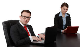 Young Business Couple on Laptops. Young business colleagues working on their laptops at the office desk, isolated against a white background.The focus is Royalty Free Stock Images